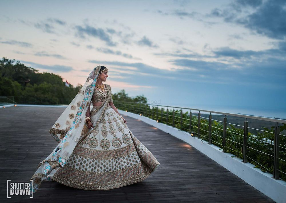 Photo of bride twirling in a pastel bridal lehenga