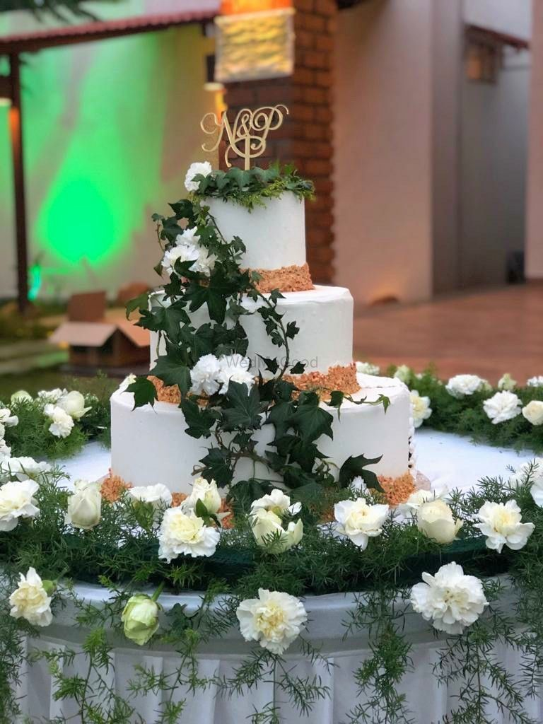Photo of Three-tiered wedding cake with foliage and flowers.