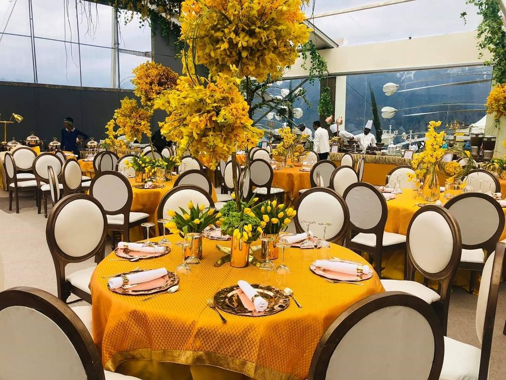 Photo of Table settings done with yellow table spreads and wooden chairs.