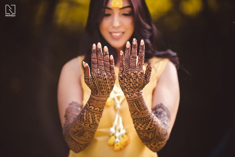 Photo of Bride showing off mehendi portrait