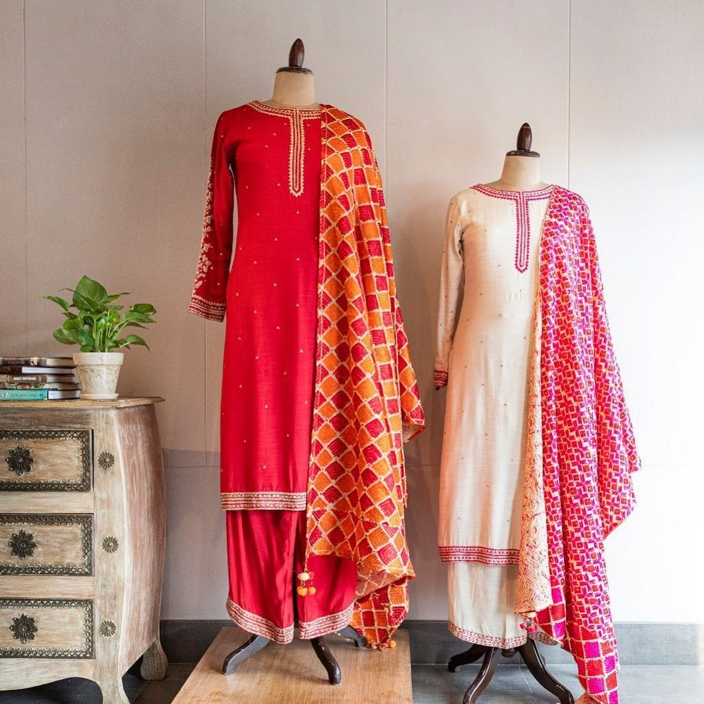 Photo of Bright pink straight suit with orange and pink phulkaari dupatta. Ivory straight suit with contrasting pink banarasi dupatta.