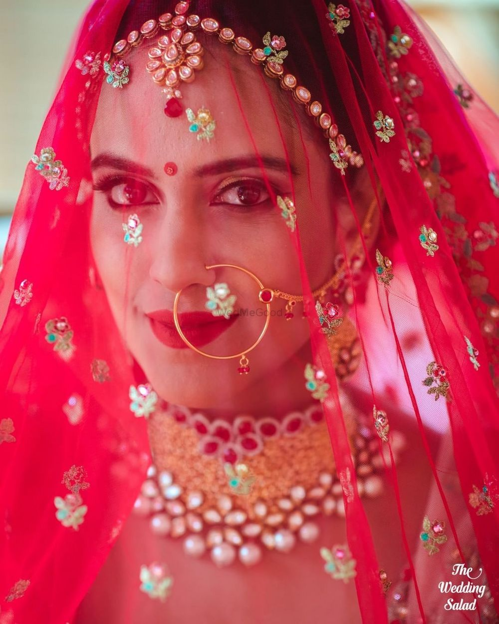Photo of bride with her dupatta as a veil shot looking into camera