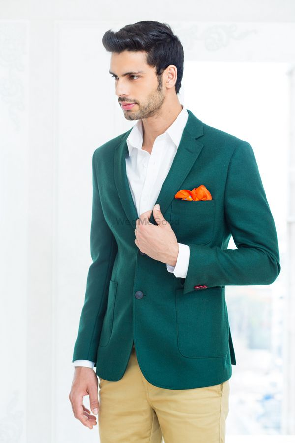 Photo of jade green aquamarine velvet jacket with tangerine orange hankerchief and beige pants