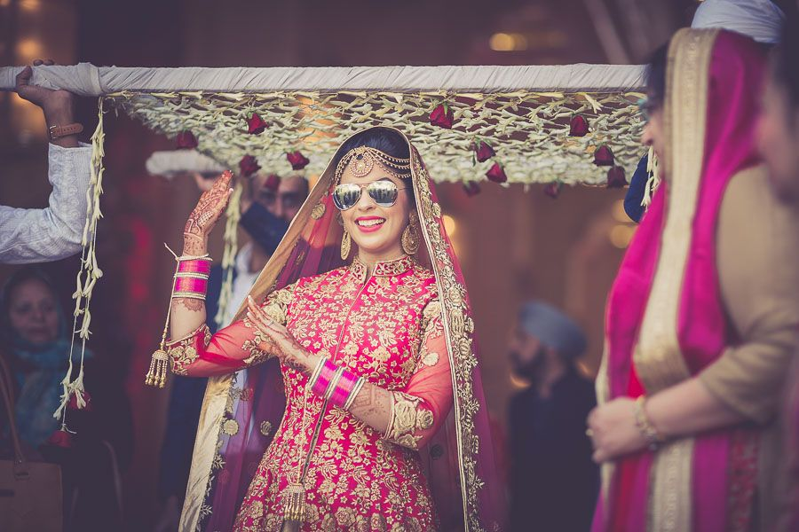 Photo of Cool bride dancing and entering wearing sunglasses