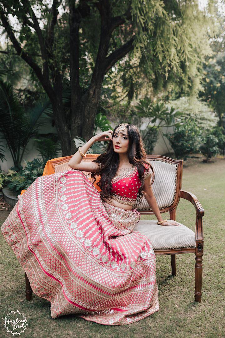 Photo of Bride posing in bright pink gota patti lehenga