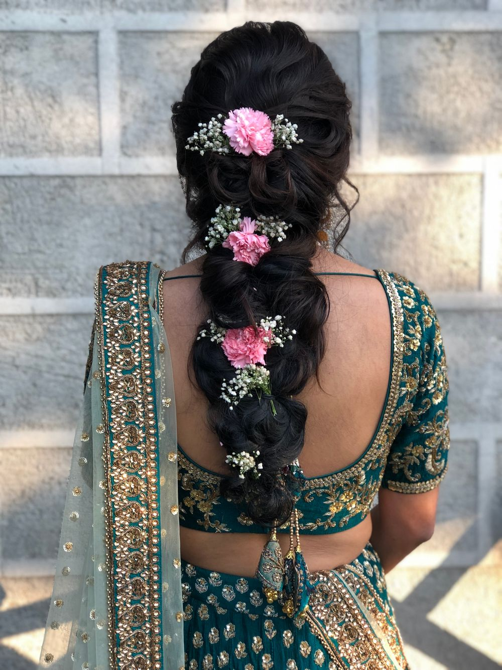 Photo of Braided hairdo with baby's breaths and pink carnations.