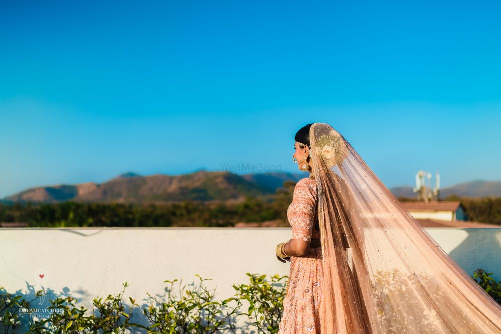 Photo of Pastel white bridal bun with peach lehenga
