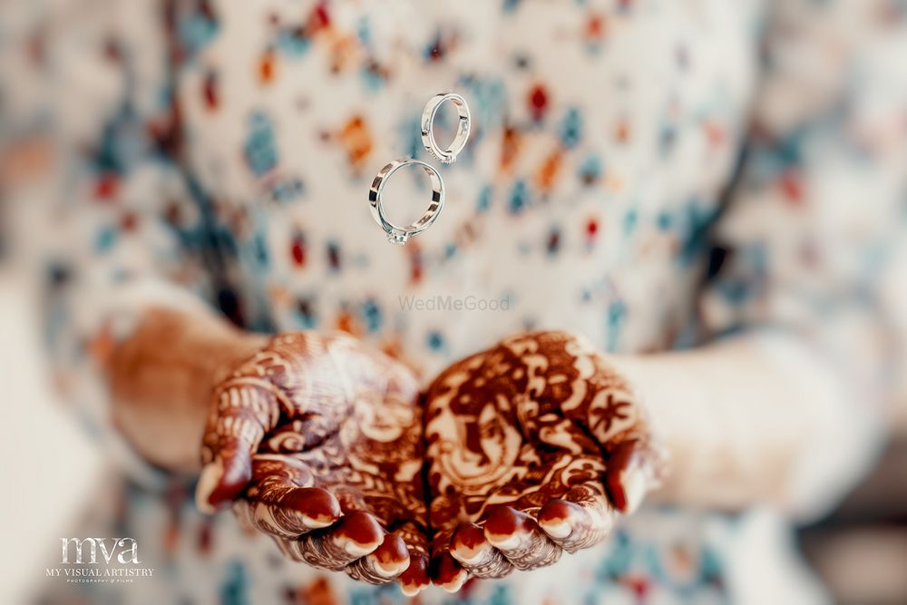 Photo of Bride tossing engagement rings with mehendi laden hands