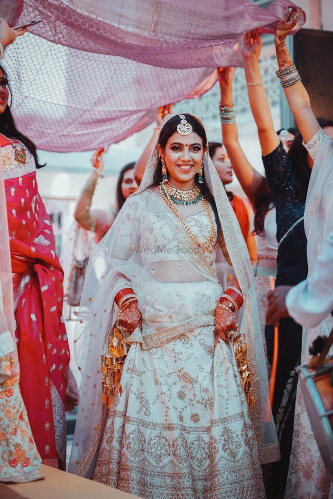 Photo of Bridal entry under a traditional phoolon ki chaadar.