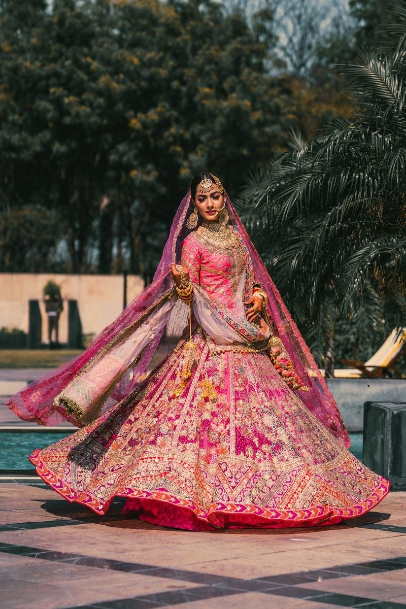 Photo of Bride twirling in heavy pink lehenga.