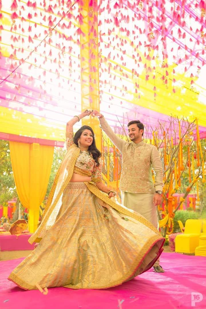 Photo of A couple in coordinated outfits dancing on their mehndi day