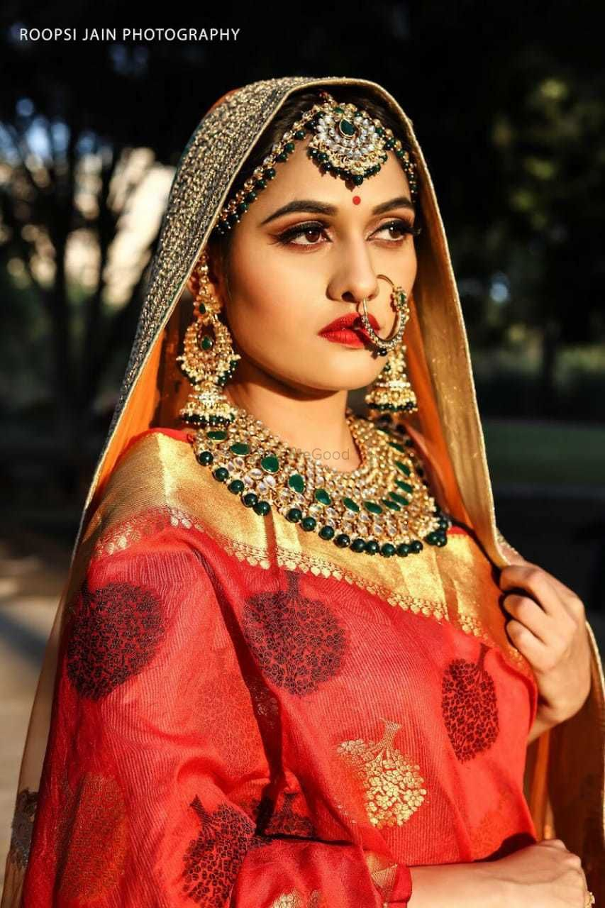 Photo of Pretty bride wearing red lehenga with gold and green beads jewelry
