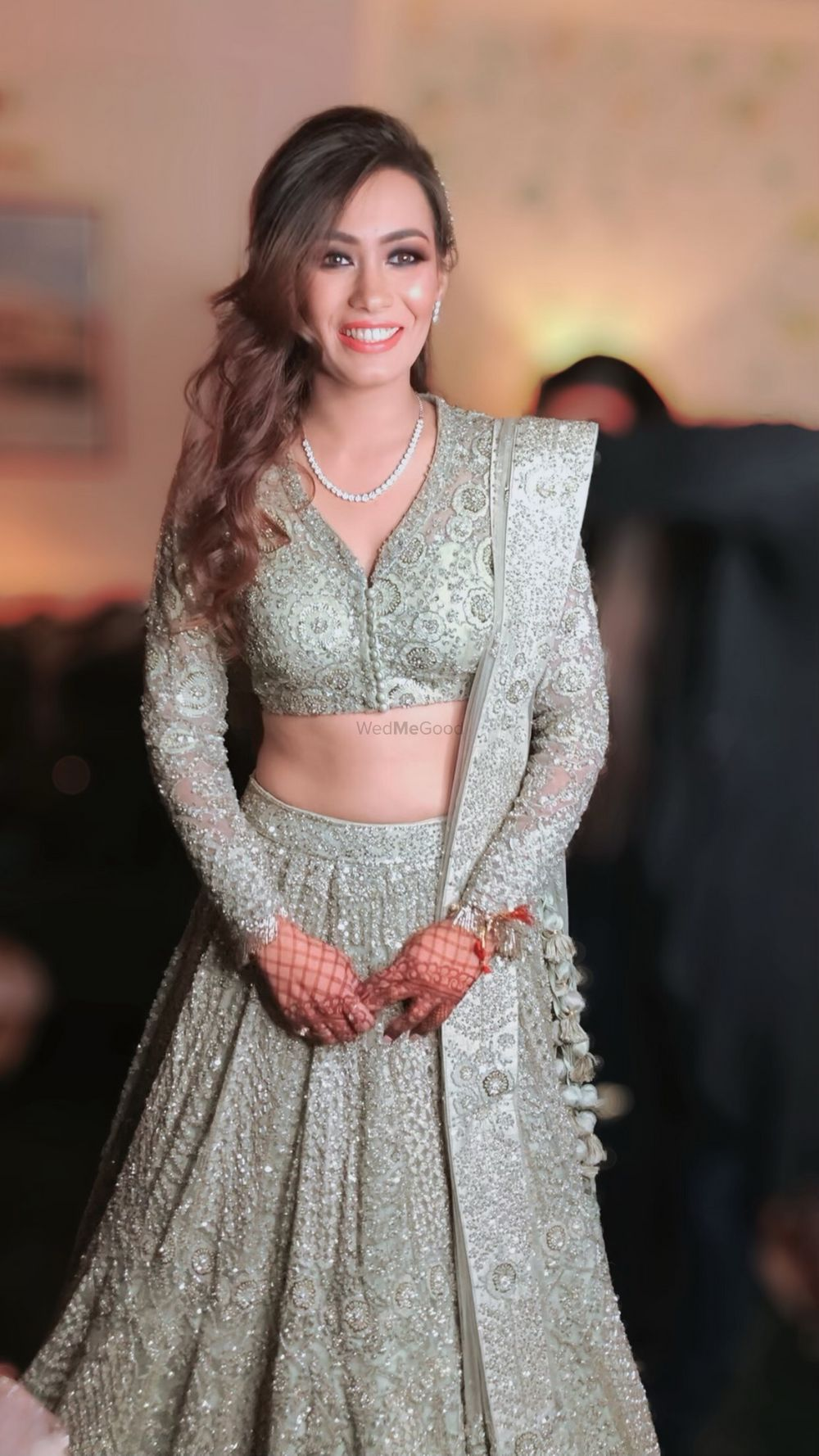 Photo of A bride in a silver lehenga wearing light, nude makeup.