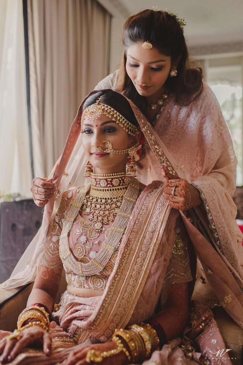 Photo of Bride with sister dupatta placing on head shot