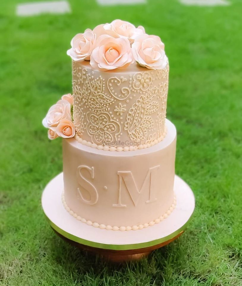 Photo of A pastel pink cake decorated with florals and the couple's initials.