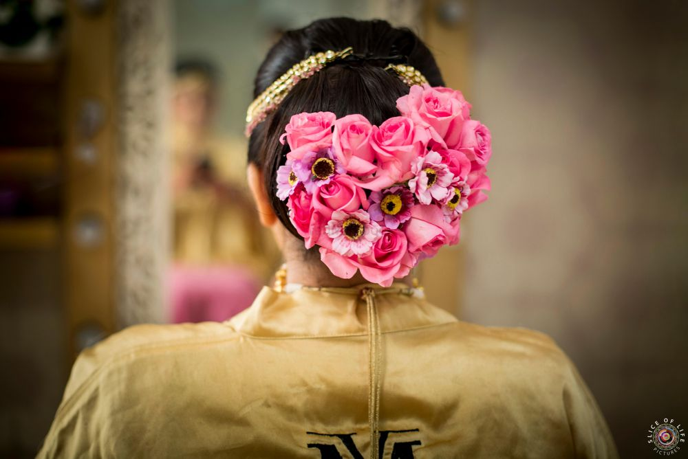 Photo of Bright pink bridal bun with big flowers