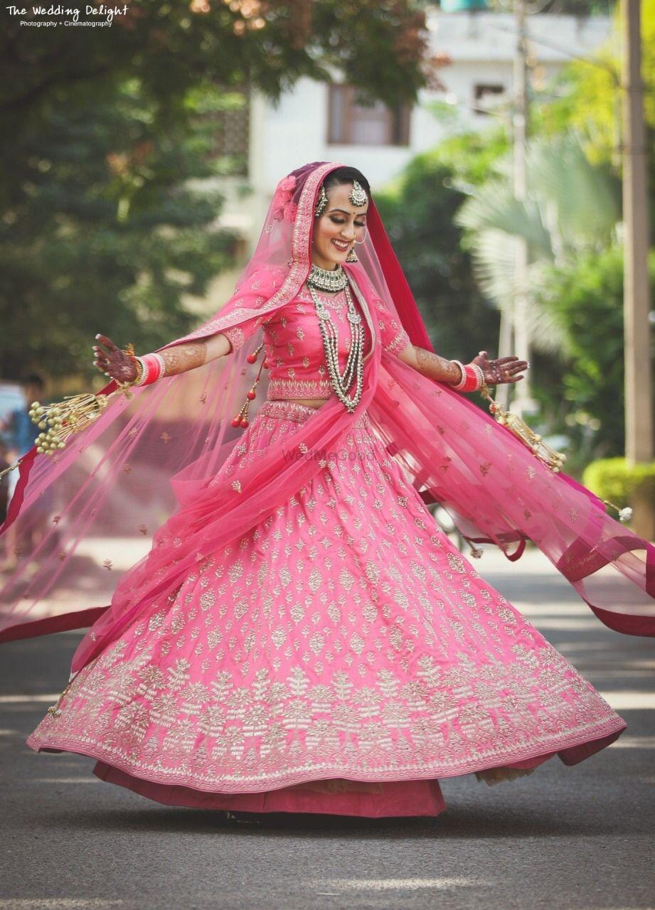 Photo of Sikh bride in bright pink lehenga twirling