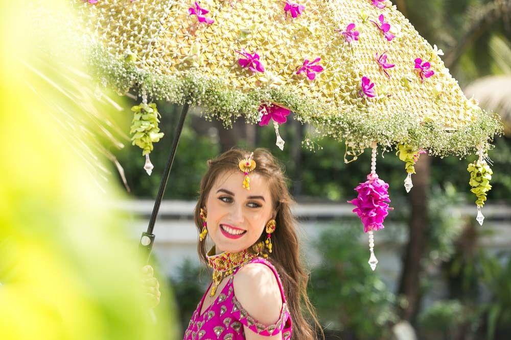 Photo of Bride entering under a floral umbrella on mehendi