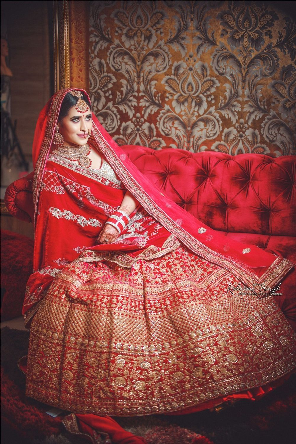 Photo of Bride sitting on sofa in bright red and gold lehenga
