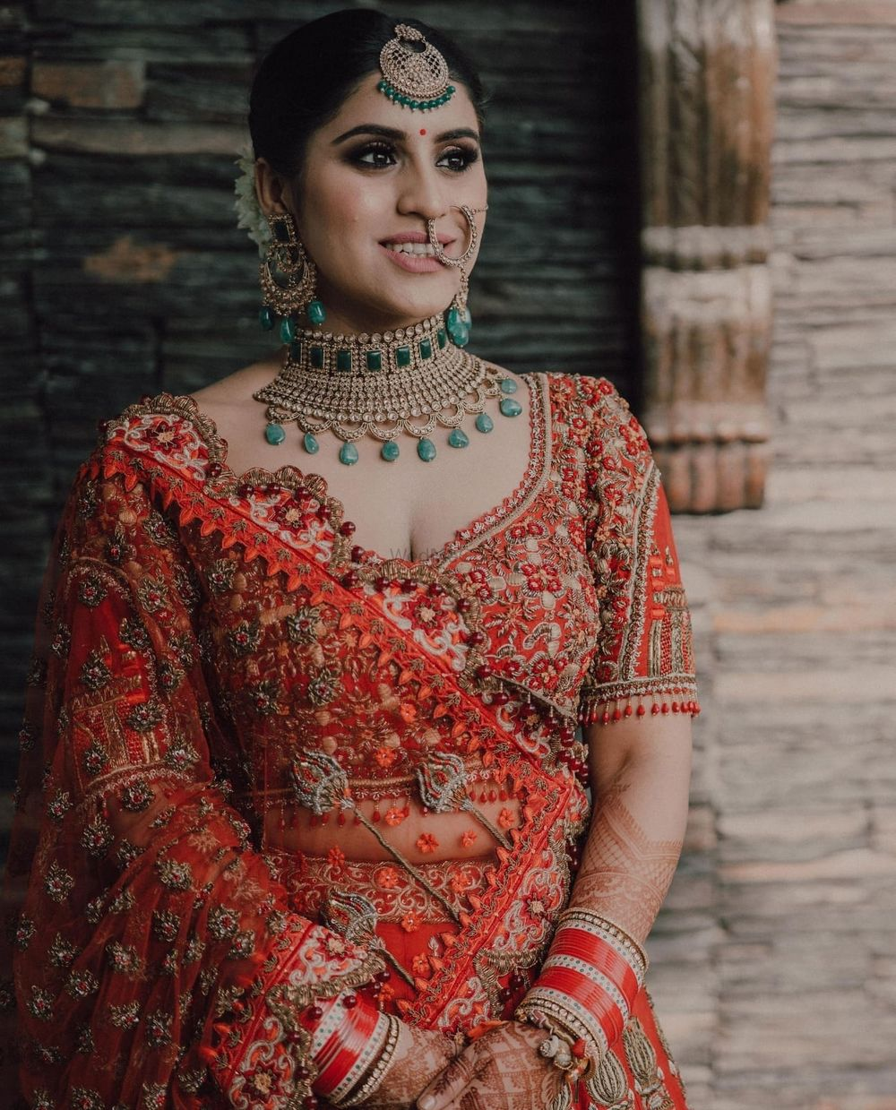 Photo of Bride wearing a red lehenga and posing on her wedding day.