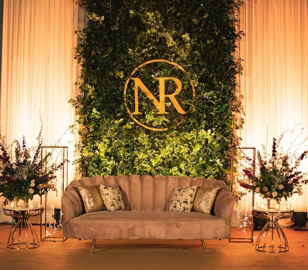 Photo of light green and gold couple seating idea with botanical wall