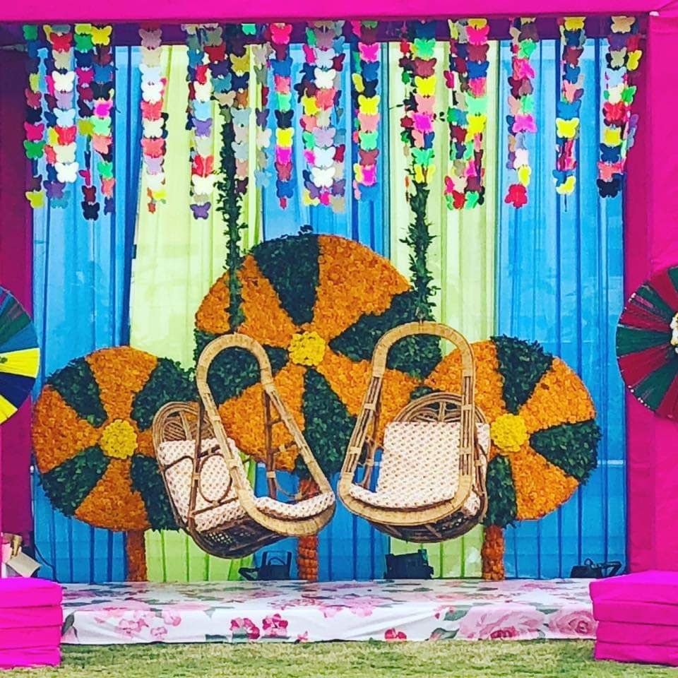 Photo of Colorful mehendi decor with swing for the bride