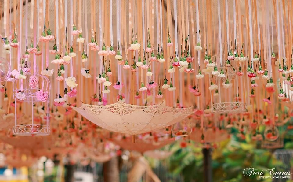 Photo of Beautiful peach decor with suspended umbrella and bird cage for mehendi