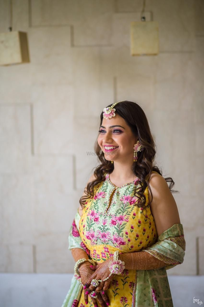 Photo of A bride in a light lehenga and floral jewellery for her mehndi