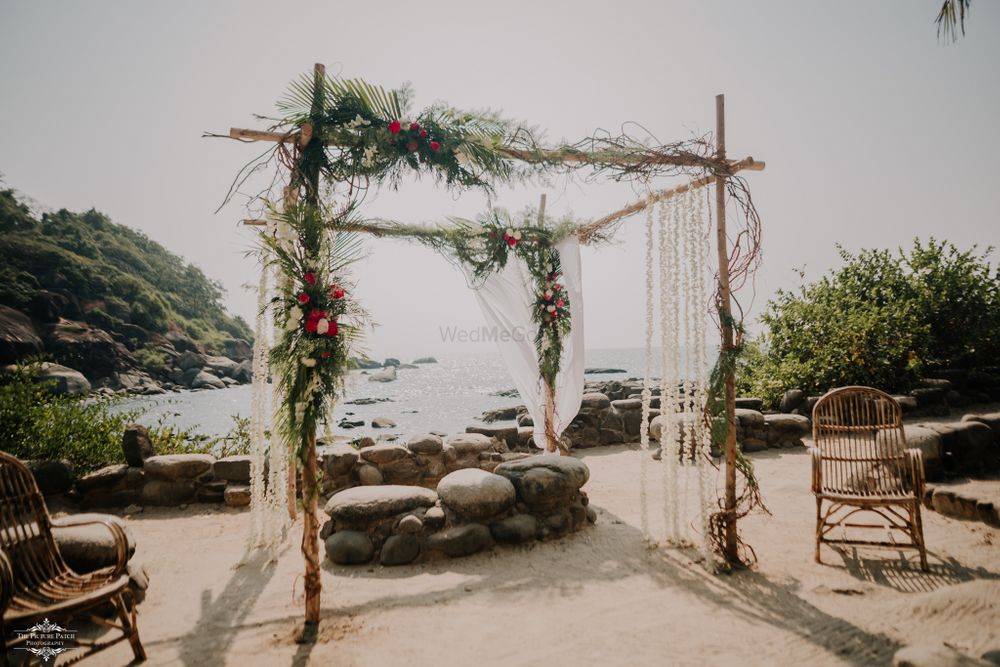 Photo of Open mandap with rustic touches and pretty floral arrangements.