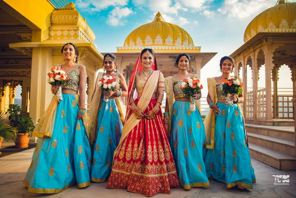 Photo of Bridesmaids in same outfits holding bouquet with the bride.