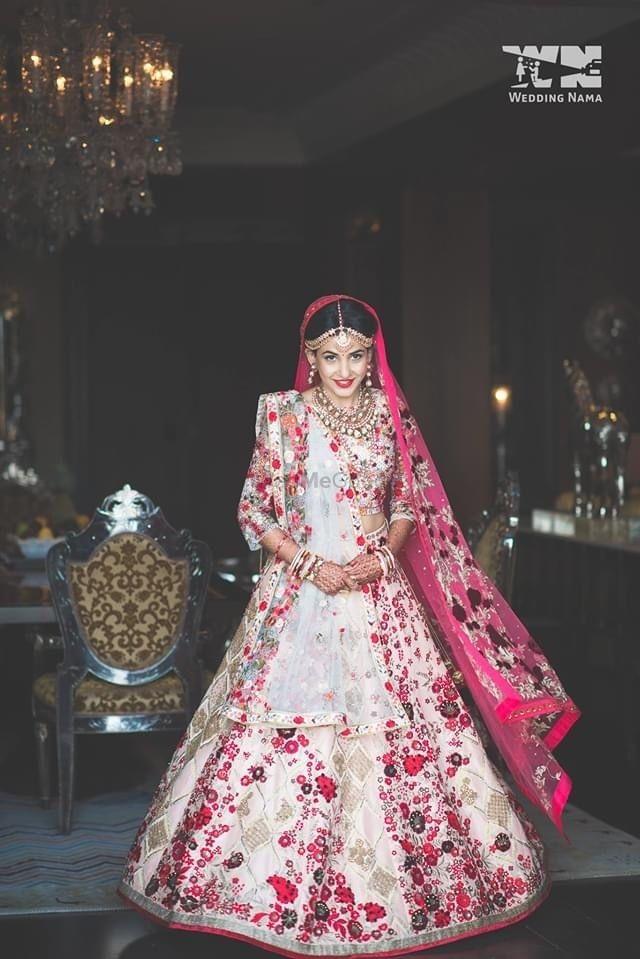 Photo of Bride wearing a multi-coloured lehenga.