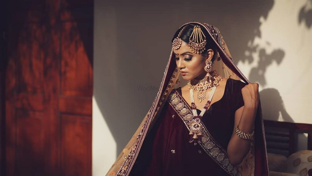 Photo of Bride in a stunning maroon lehenga.