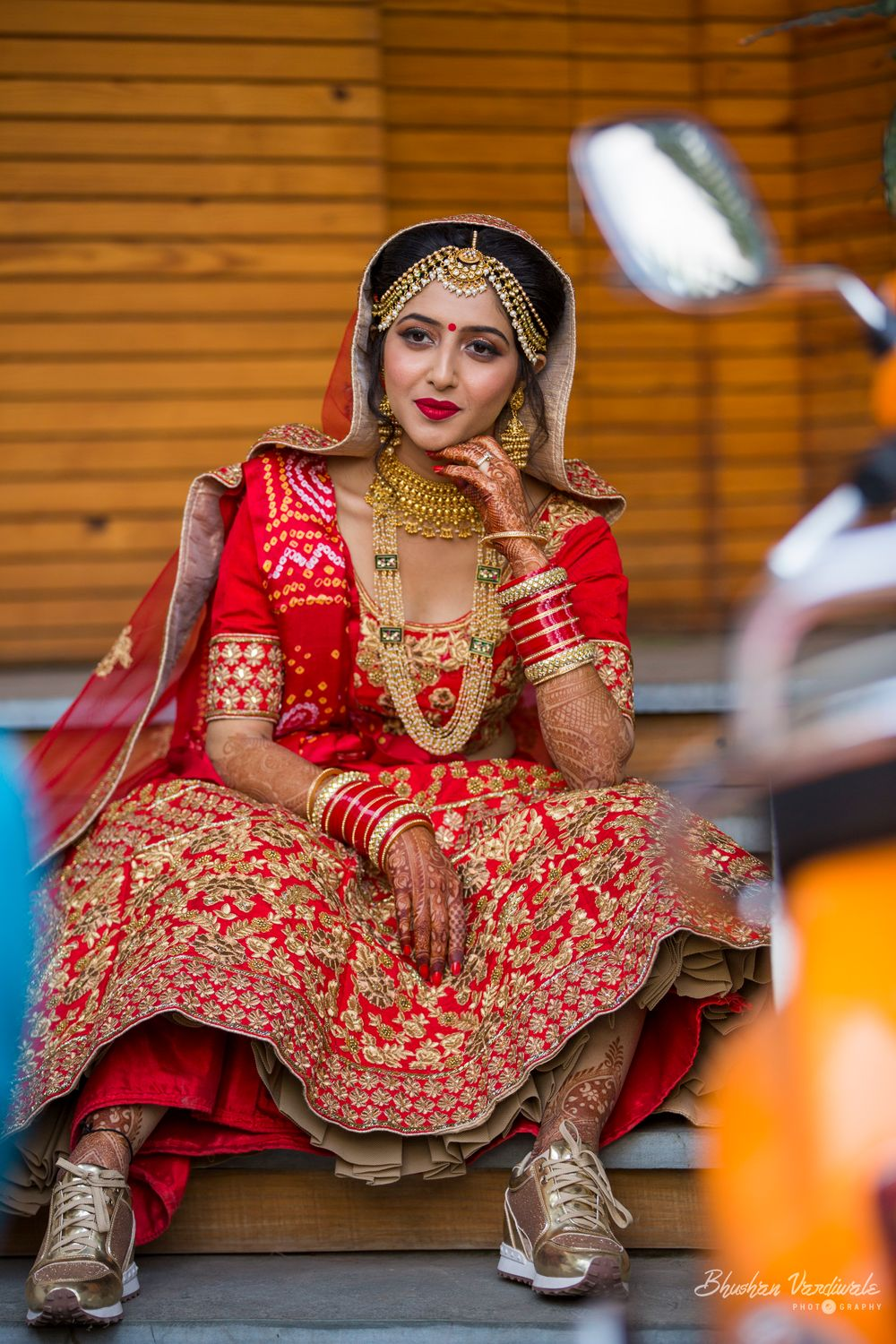 Photo of Cute bride wearing sneakers under her bridal lehenga