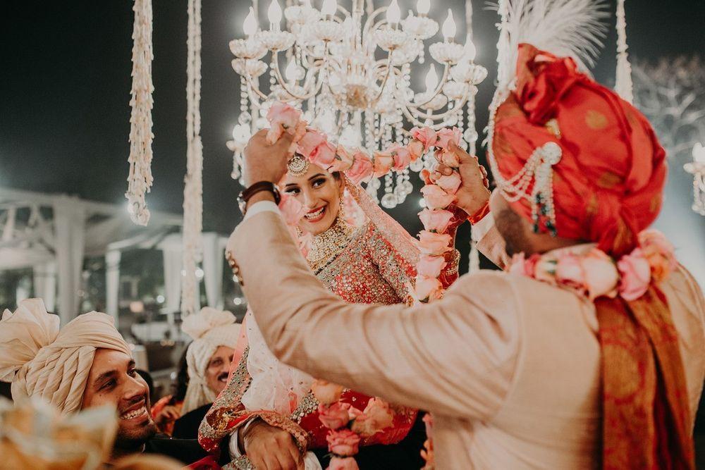 Photo of happy couple during the jaimala shot