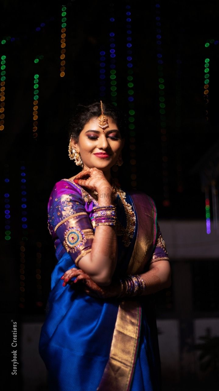 Photo of South Indian bride wearing a royal blue saree with a purple blouse.