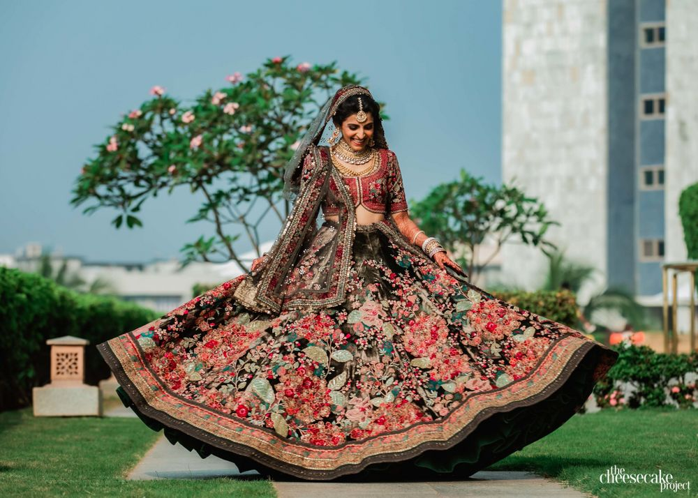 Photo of Bride twirling around in her floral bridal lehenga.