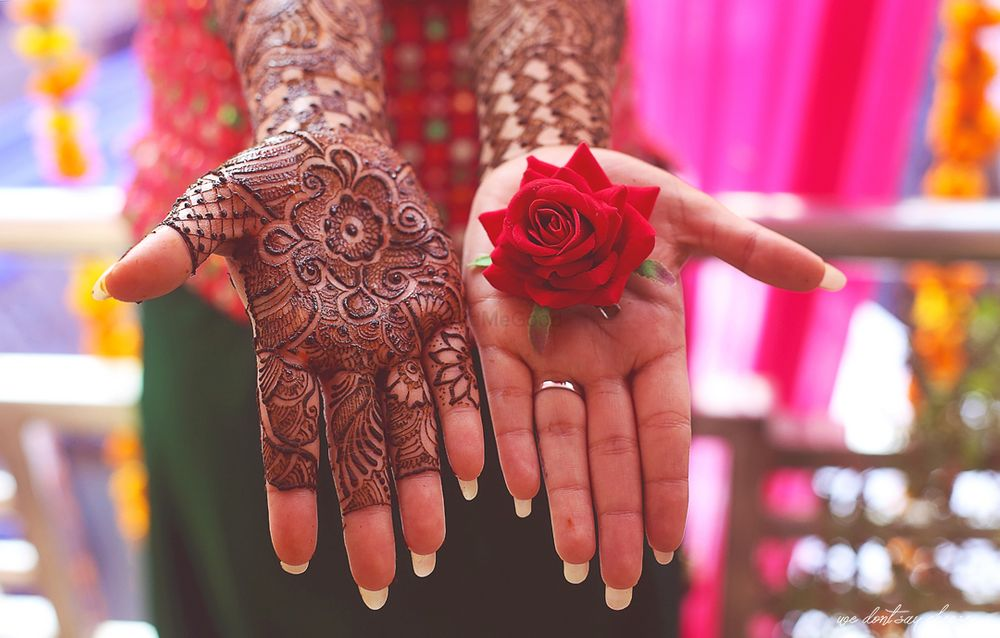 Photo of Mehendi on one hand rose on other
