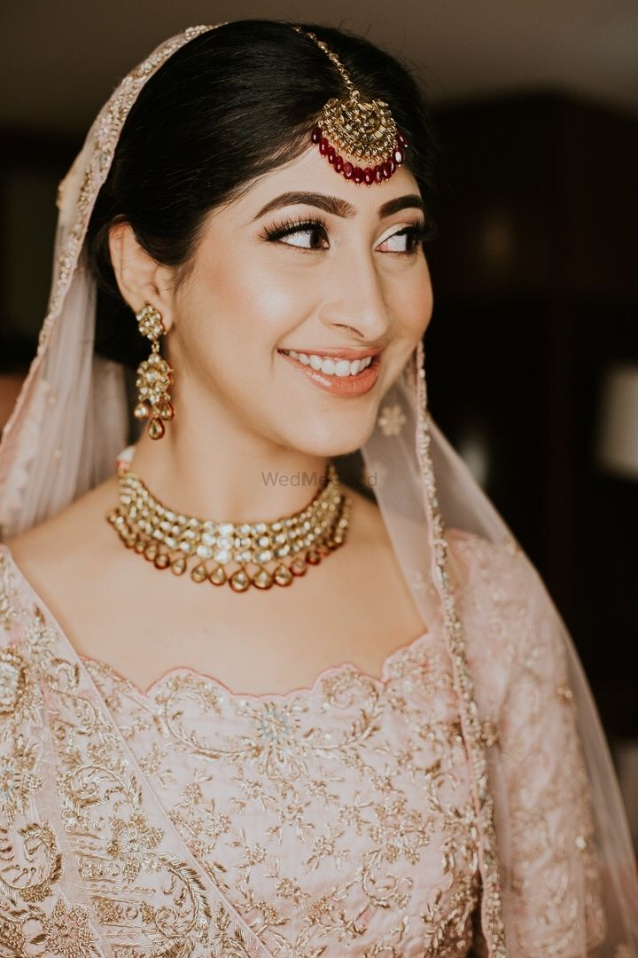 Photo of A happy bridal shot in a beautiful pastel lehenga and subtle makeup.