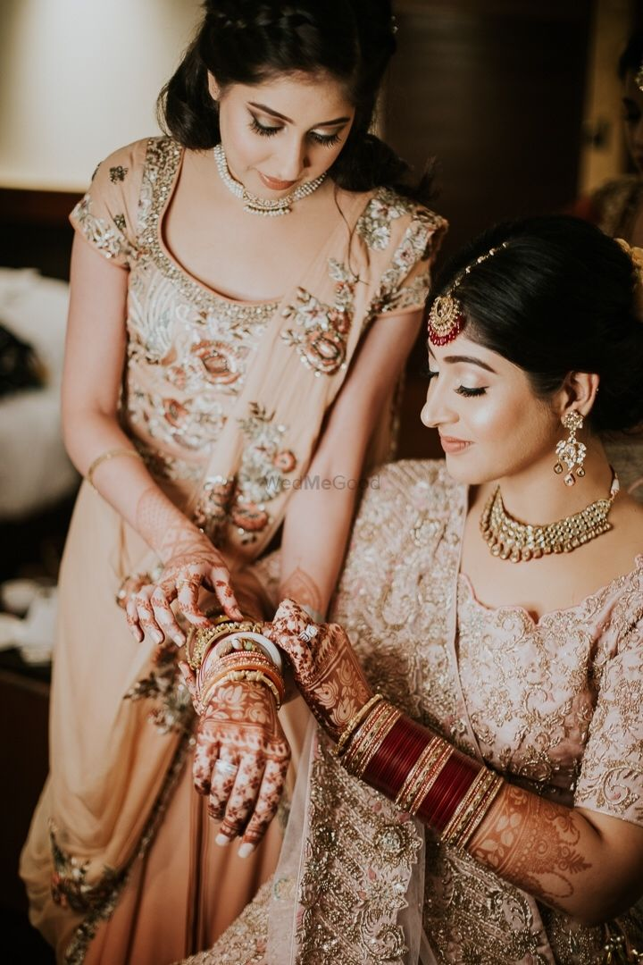 Photo of Bride with sister on her wedding in light lehengas and subtle makeup.