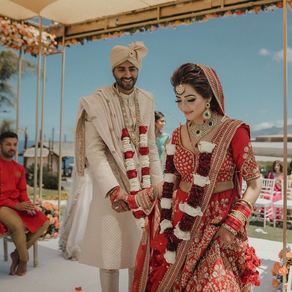 Photo of Candid shot of bride and groom taking pheras