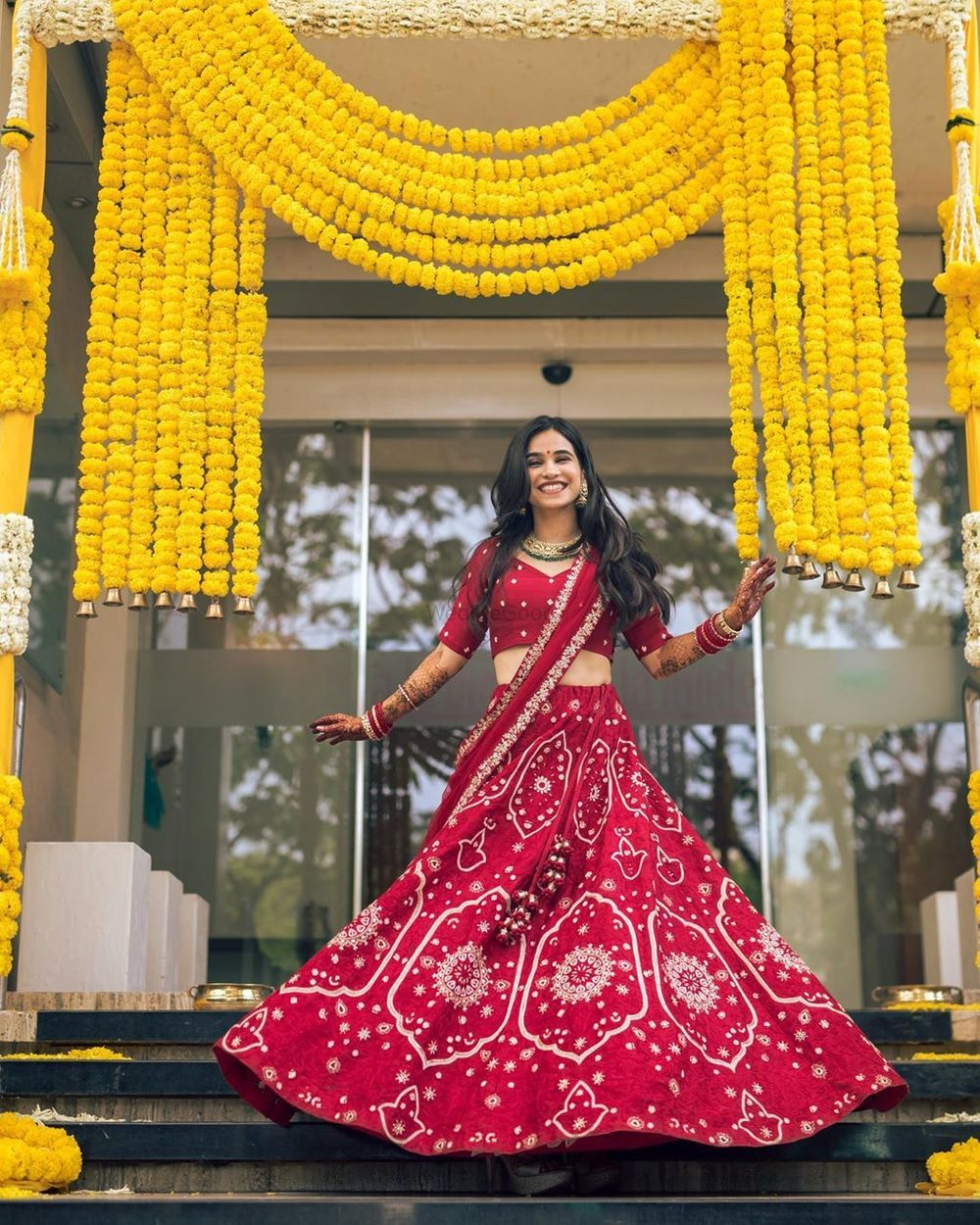 Photo of Bride twirling in her red lehenga.