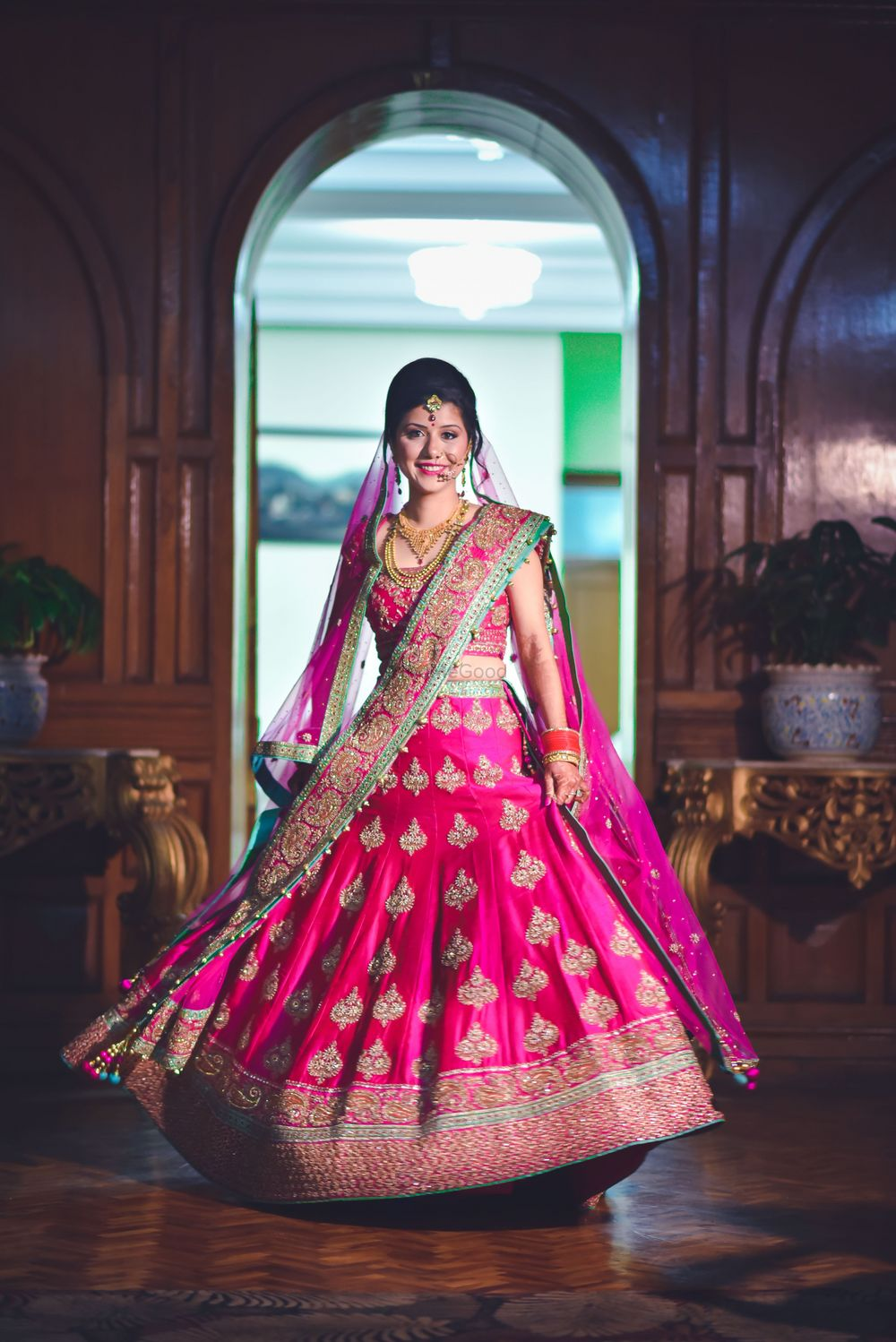 Photo of Bride twirling in red lehenga with gold motifs