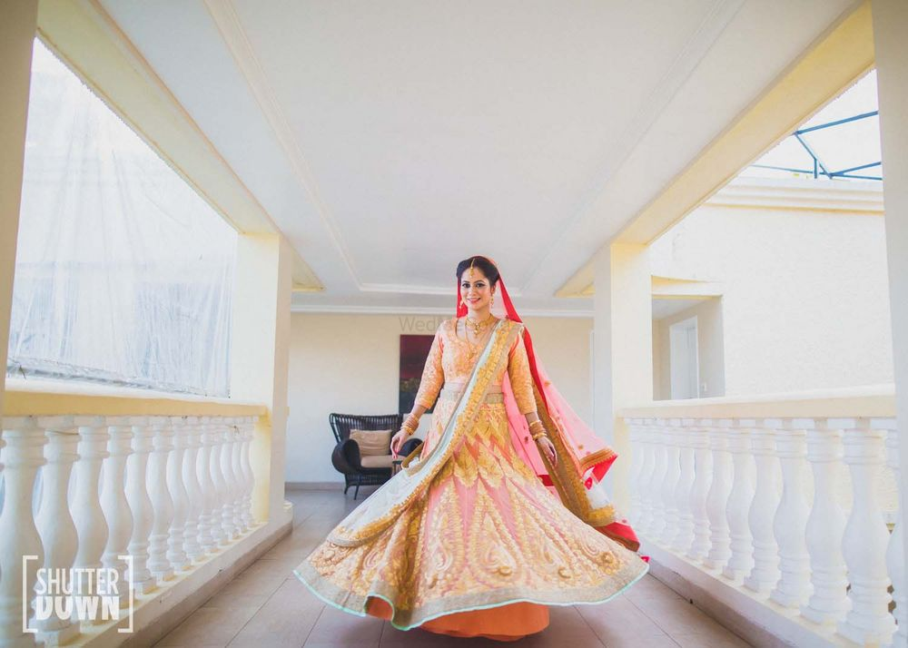 Photo of twirling bride shot in peach and gold lehenga