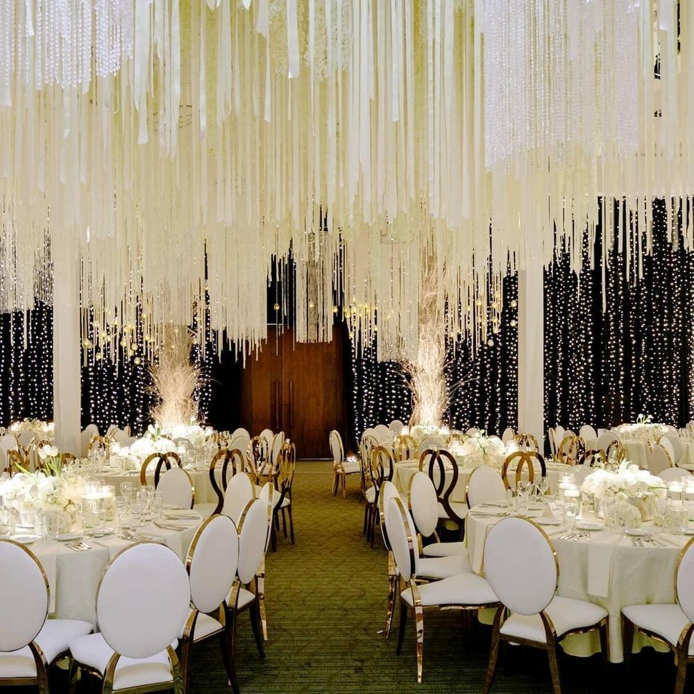 Photo of White and gold table settings with fringes as ceiling decor.