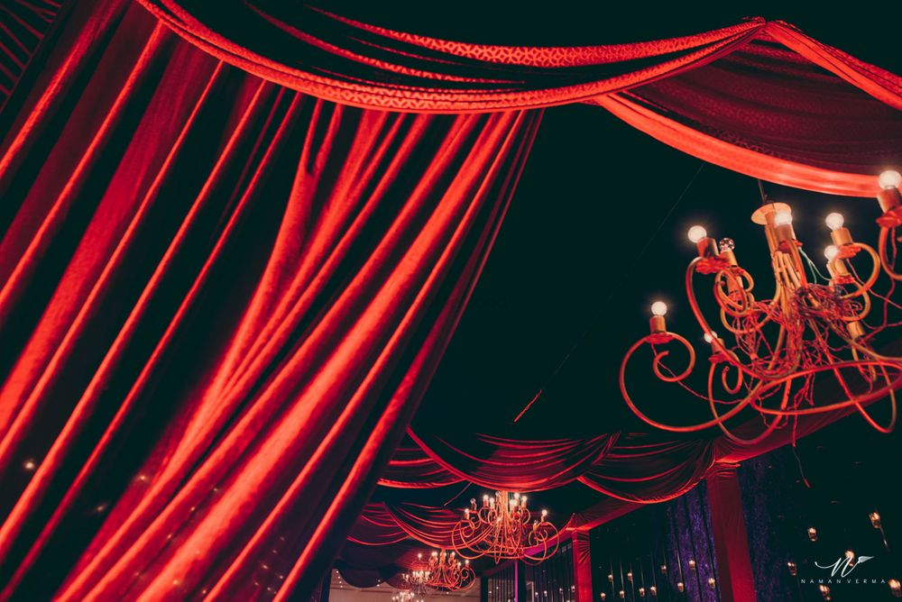 Photo of Glam red decor theme with wrought iron chandeliers