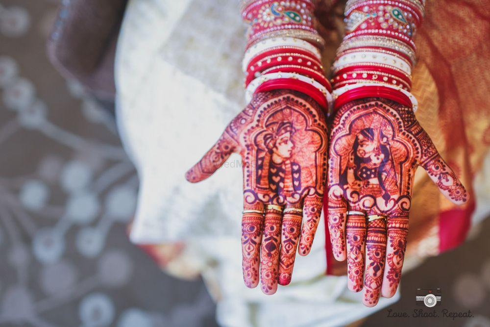 Photo of Traditional design mehendi with bride and groom portraits