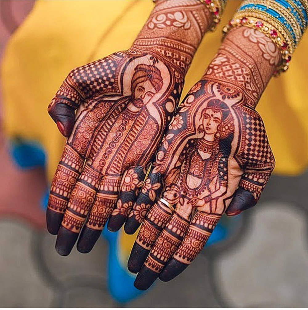 Photo of Intricate hand mehndi design with bride and groom portrait