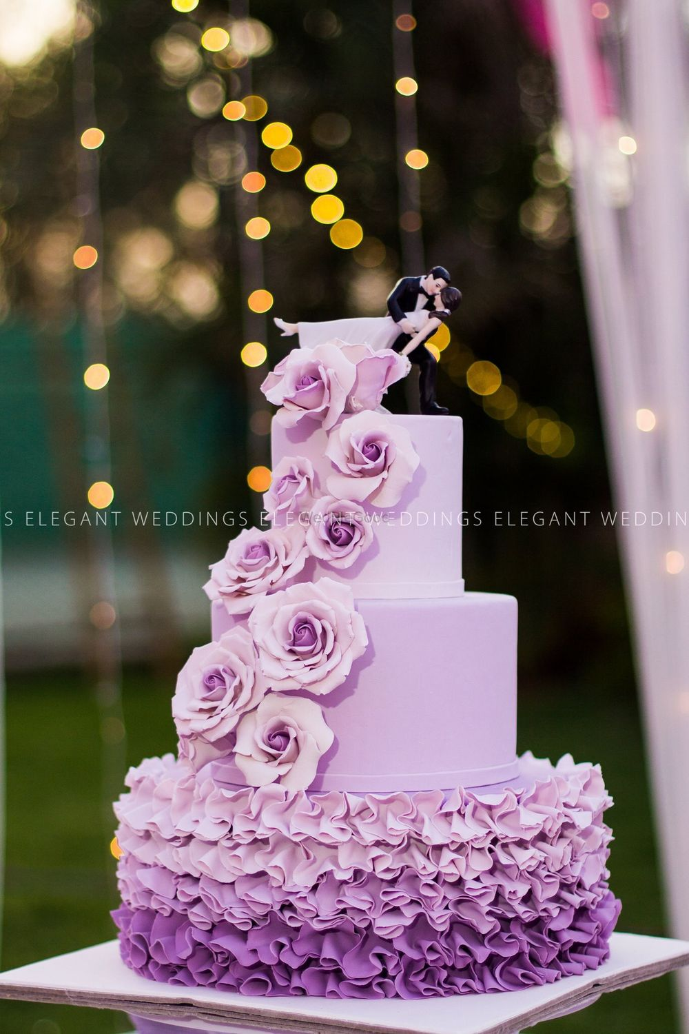 Photo of Ombre lavender 3 tiered wedding cake with bride and groom topper