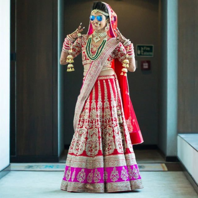 Photo of Bride in red and pink bridal lehengas wearing reflectors