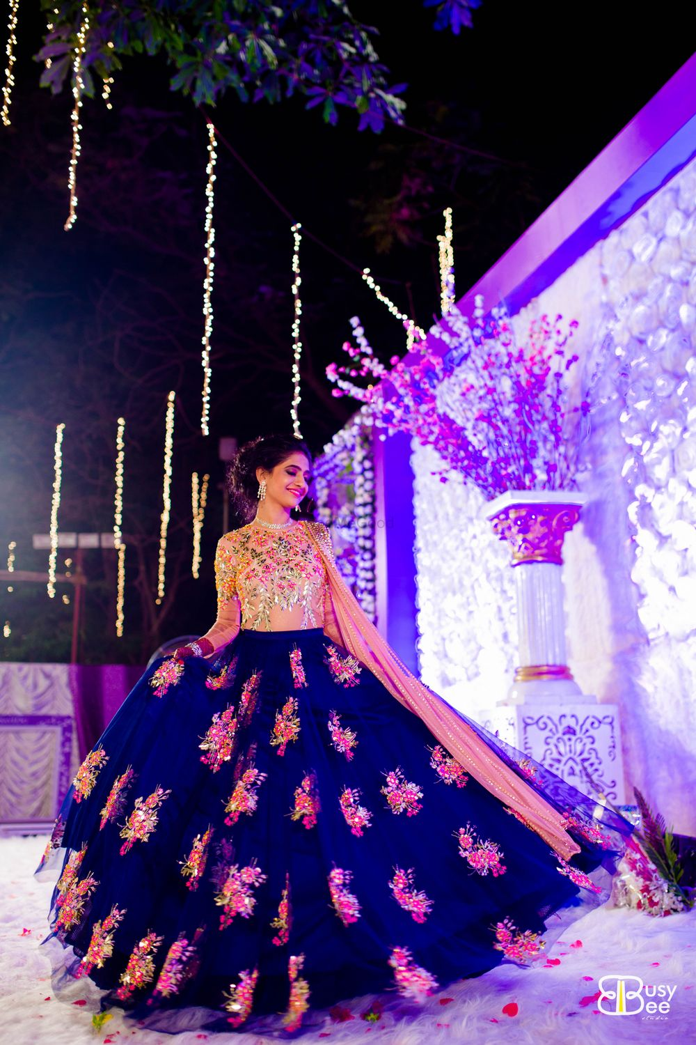Photo of Bride twirling in blue floral print lehenga